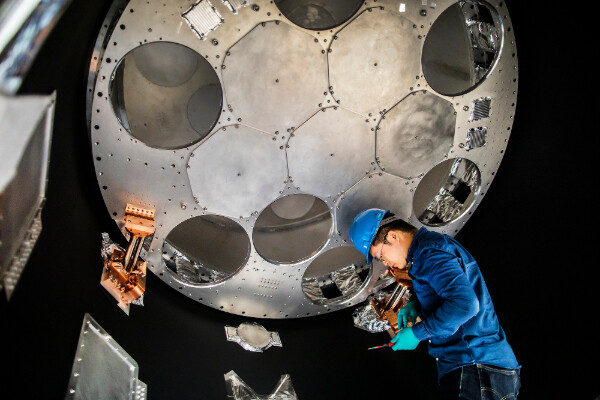 a person in a hard had working inside a large telescope detector