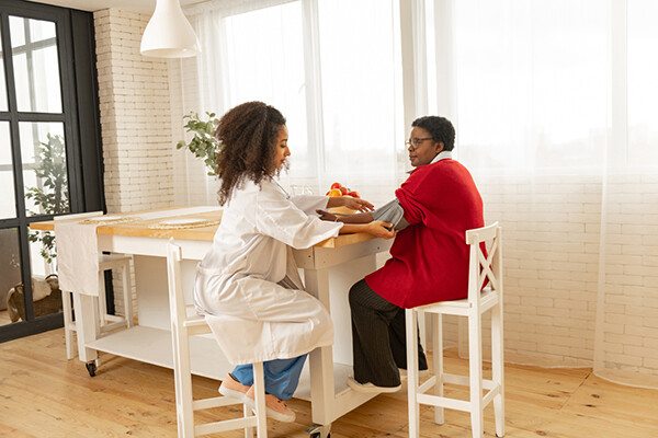 A home health care aide sits at a kitchen table with a person and applies a blood pressure cuff, home health visits reduce sepsis readmission.
