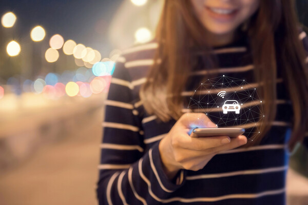 Person holding a cellphone with a lit up image of a car emanating from it.