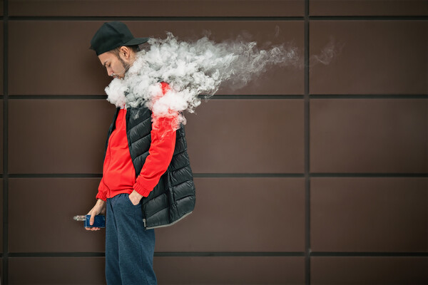 Side-view of person against a wall exhaling smoke from an e-cigarette