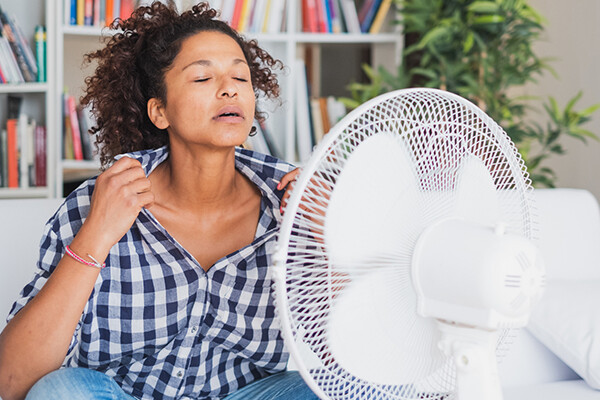 A person sits in front of a fan holding shirt front open to cool off, indicating rising temperatures