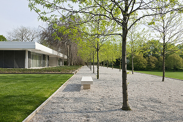 Exterior view of Miller House, with a pebble courtyard with trees and a bench, green lawns and a modernist home.
