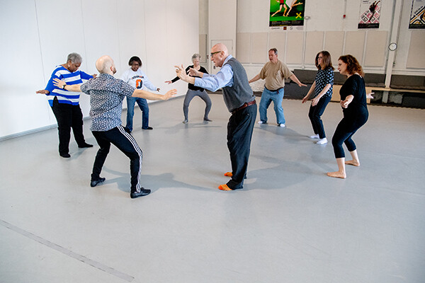 A group of people with Alzheimer's and an instructor stand in a circle in a large dance studio with their arms outstretched, bending their knees.