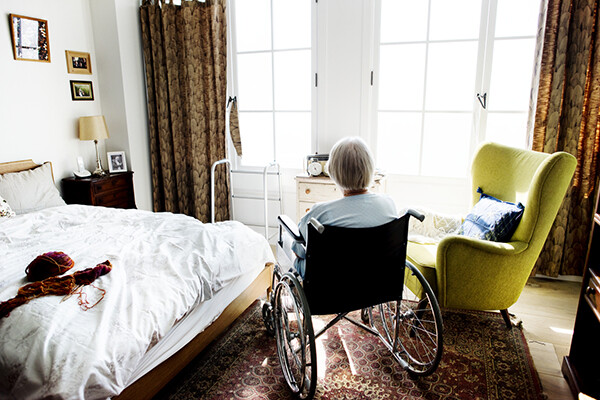 person in wheelchair looks out the window, elder in an eldercare facility with a lack of nurses present.