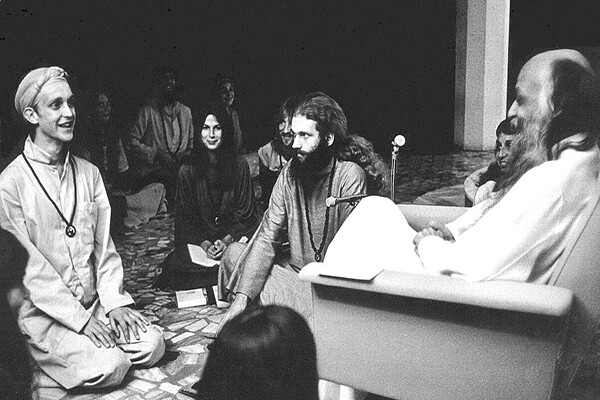 Osho seated with disciples kneeling before him, circa 1980s