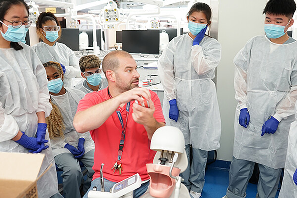 A Penn Dental Medicine instructor sits with a dental model tool in hand beside a replica of head with an open mouth while seven high school students in white lab coats, gloves and masks watch the demonstration.