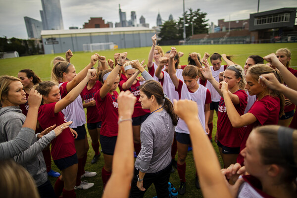 Players on the women's soccer team gather in a circle with their fists raised with their coach at practice.