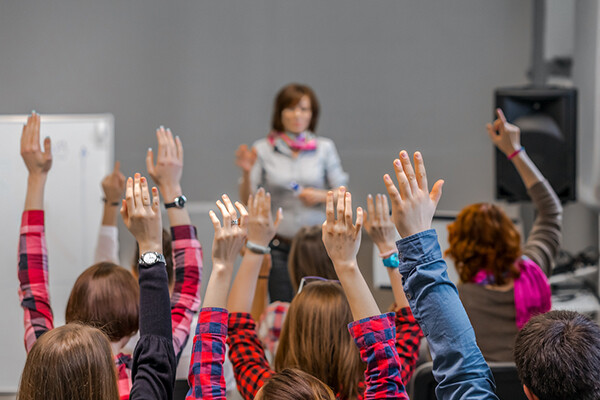 Seated students in a classroom raise their hands while a teacher stands at the head of the classroom
