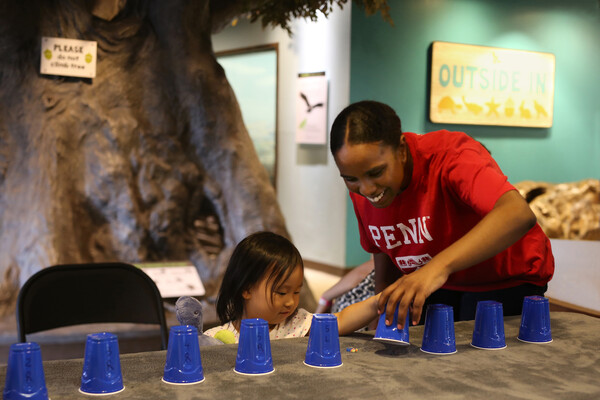 A young child at a table with an adult, playing a game with blue plastic cups.