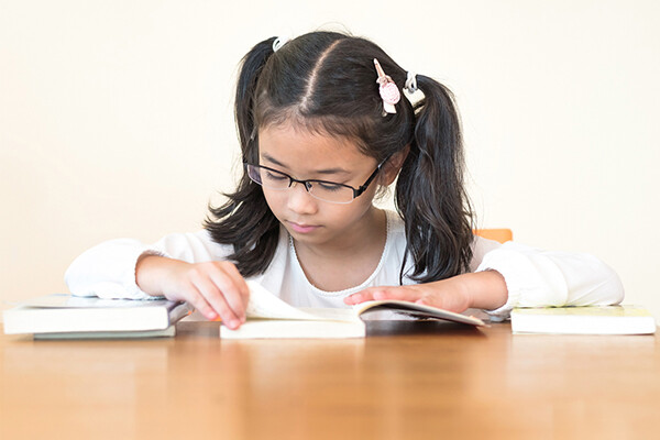 A child sits at a table reading a book, two closed books are on the table beside them.