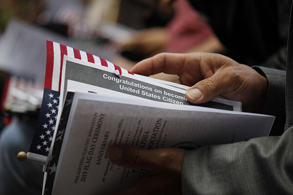 closeup of new citizen handbook and a flag in the hands of a new U.S. citizen