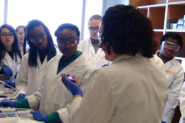 high school students in lab coats face an instructor in a reproductive science lab.