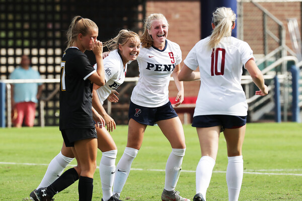 A trio of players of the Penn women's soccer team celebrate on Rhodes Field against Towson.
