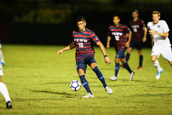 Joey Bhangdia, a midfielder on the men's soccer team, dribbles the ball down the field.