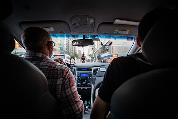 Uber or Lyft driver in traffic with a passenger in the backseat, view from backseat out the windshield