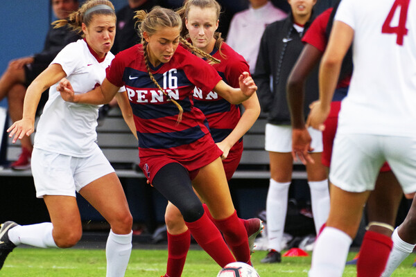 Junior midfielder Breukelen Woodard of the women's soccer team dribbles the ball between two defenders.