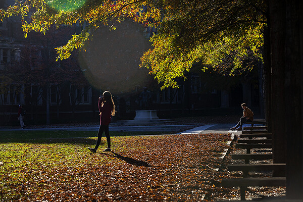Two students outside on an autumn day, one standing, one seated.