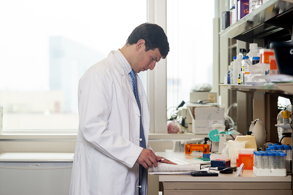 Person in a white lab coat standing at a lab bench looking at a book. Scientific materials are on the table next to and above the person.