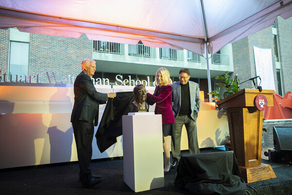 Two people pulling cloth off of bronze bust next to a podium with third person looking on