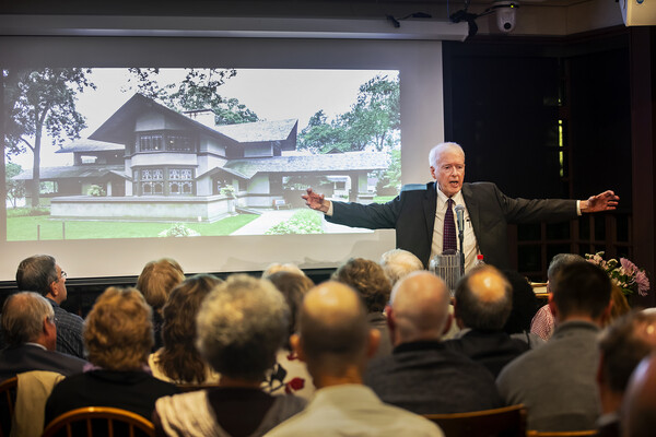 Paul Hendrickson speaking at a podium in front of a seated crowd, his arms outstretched, with a photo of a house on the screen behind him.