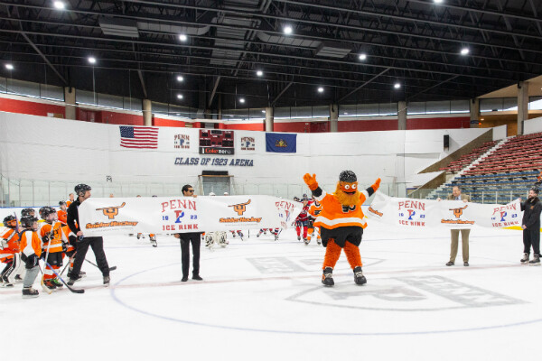 Gritty skates through ceremonial ribbon at Penn Ice Rink.