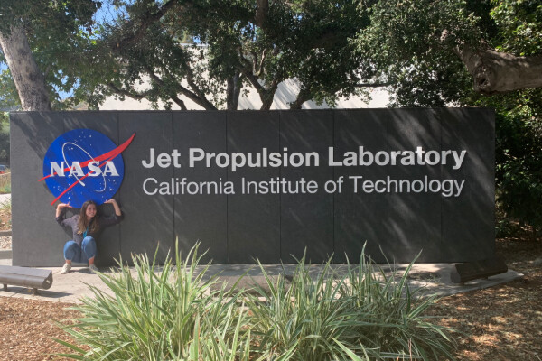 alex ulin standing in front of the jet propulsion laboratory sign, under the nasa logo and next to text that reads california institute of technology
