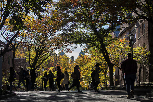 Pedestrians on Penn campus in the autumn sun with fall leaves.