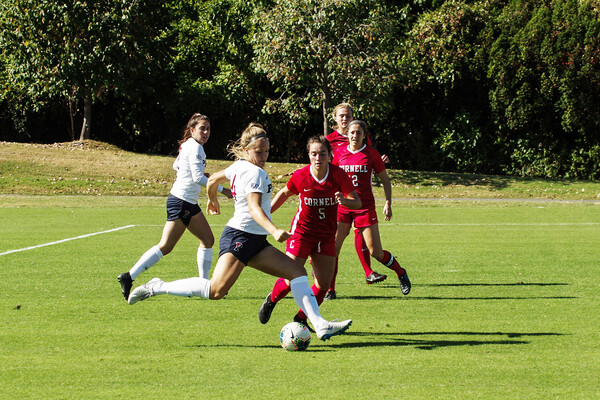 At Rhodes Field, a member of the women's soccer team dribbles the ball near a defender.