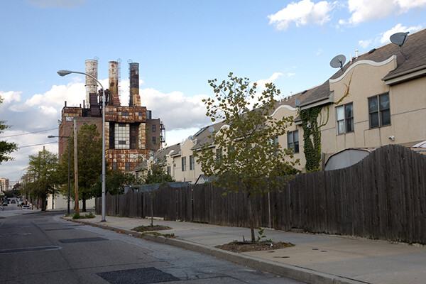 Philadelphia city street, abandoned factory in background, housing behind sidewalk fence.