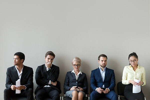 Five people sitting in chairs against a wall wearing suits waiting for a job interview.