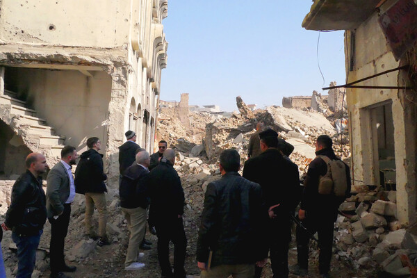 people gathered around surveying iraqi destruction