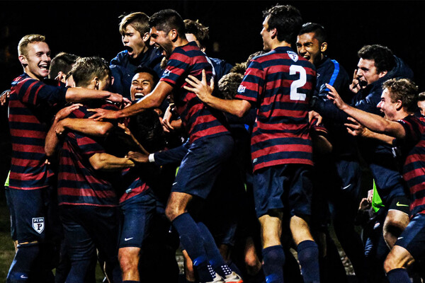 Jubilant players on the men's soccer team celebrate in a circle after defeating Yale.