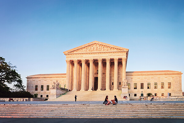U.S. Supreme Court building with people sitting on the steps and others in the background