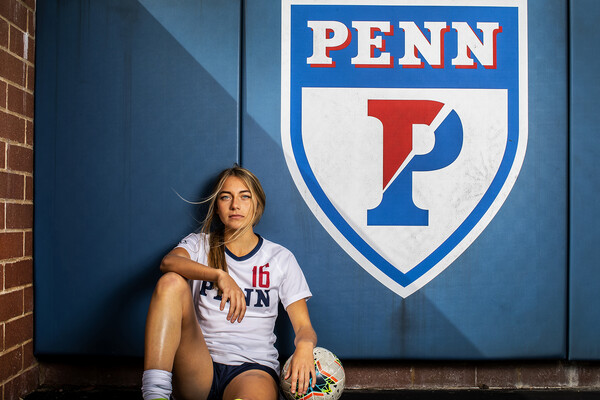 Breukelen Woodard of the women's soccer team poses sitting down near a Penn shield at Rhodes Field.