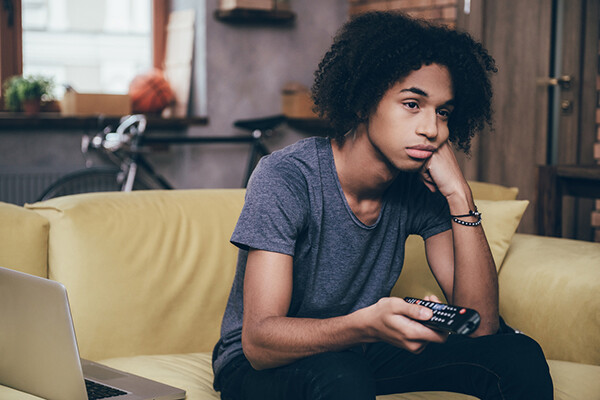 Forlorn teen sits on a couch pointing a television remote control.
