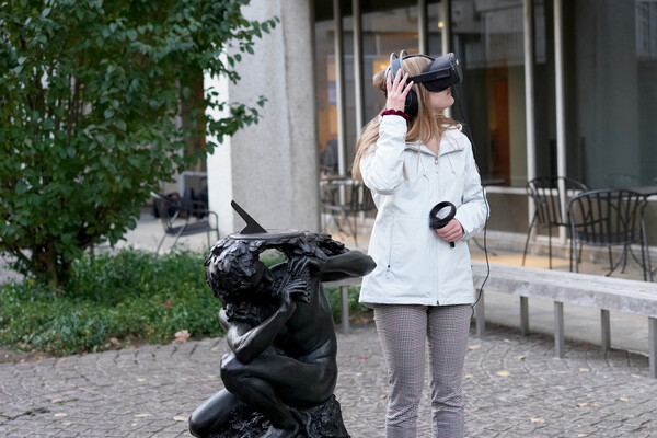 Person wearing a virtual reality headset looks to the side, standing next to a statue facing the same direction