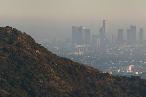 A mountain foregrounds the Los Angeles skyline, shrouded in haze