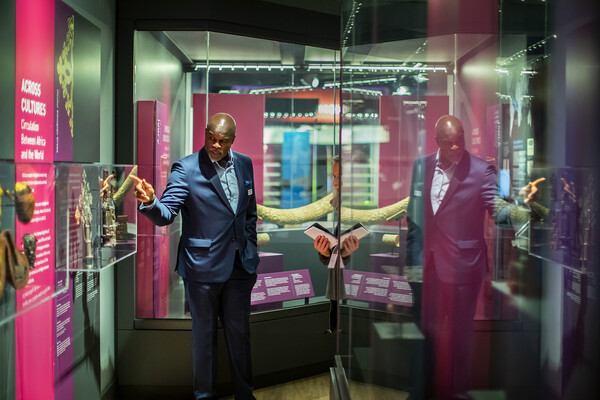 Man in a suit pointing to a glass box containing artifacts