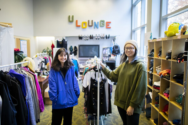 "Two people standing bewteen two clothing racks in a crowded thrift shop space. On the back wall, the word ""U Lounge"" hangs in brightly colored block letters."