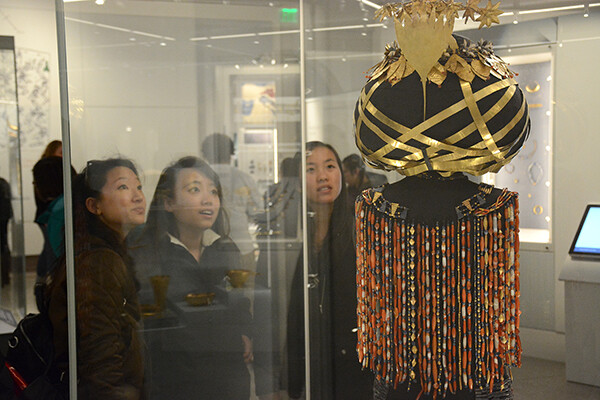 Students examine Queen Puabi's Haddress through glass case