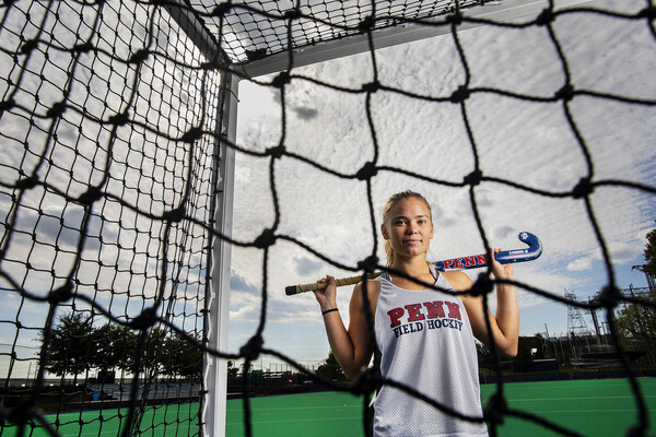 At Ellen Vagelos Field, Alexa Schneck of the field hockey team poses on the field hockey field in a net with her stick across her shoulders.