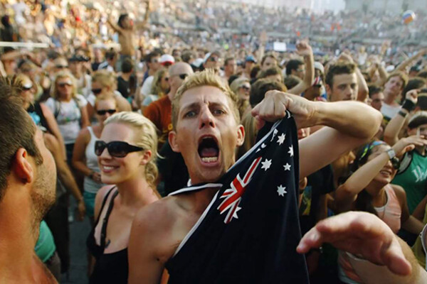 Australian person shouts while gripping flag shirt
