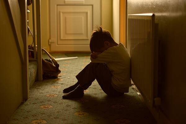 A young child sits in a hallway burying their head in their arms on a rather dirty carpet