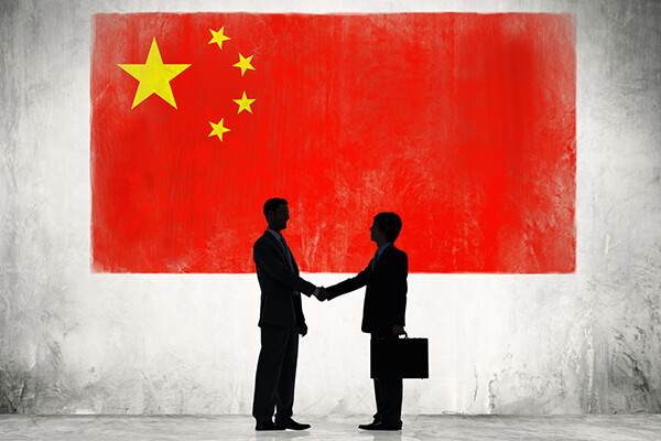 Two figures in business suits shake hands under a large Chinese flag.