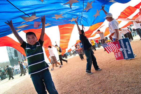 Several adolescents stand under a giant American flag like a parachute aloft at an immigration reform rally.