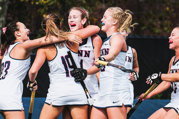 Facing Brown in Providence, field hockey team members hug each other and celebrate.