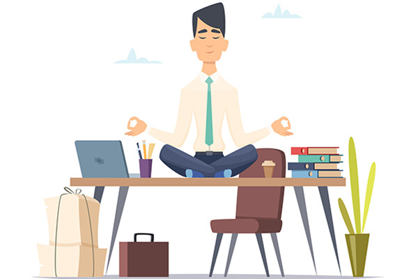 Person sitting on top of desk in meditative pose with laptop and books surrounding