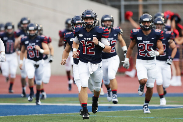 Quarterback Eddie Jenkins runs onto the field with his teammates at Franklin Field.