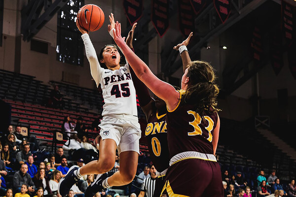 Suspending in the air against Iona at the Palestra, freshman Kayla Padilla shoots the ball between to opponents.