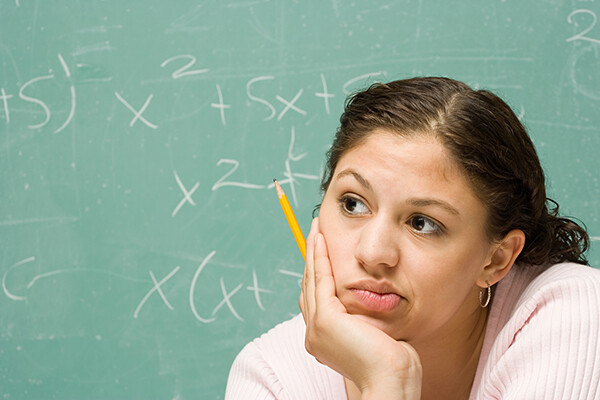 person looks perplexed holding a pencil staring into middle distancw with chalkboard behind them with math equations.